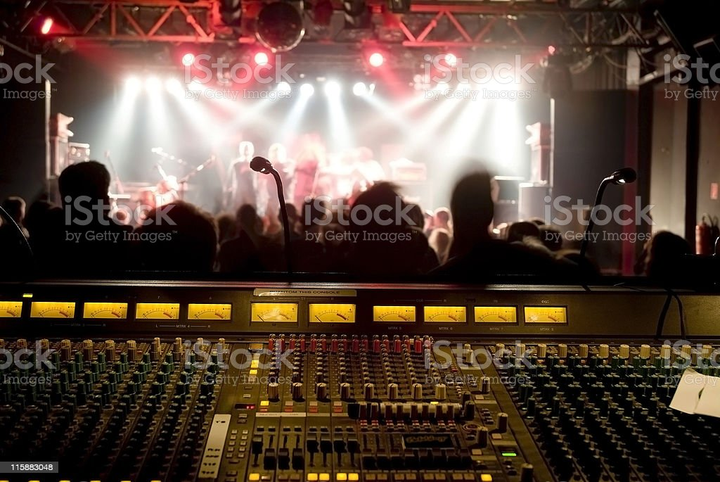 Front of house soundboard with band on stage stock photo
