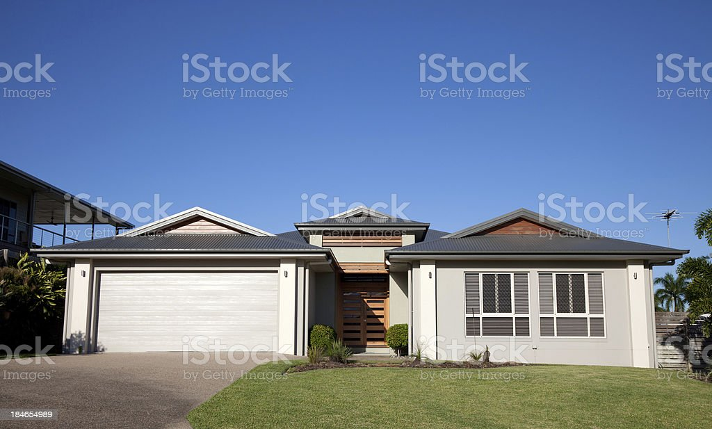 Front of modern home with green grass and blue sky stock photo