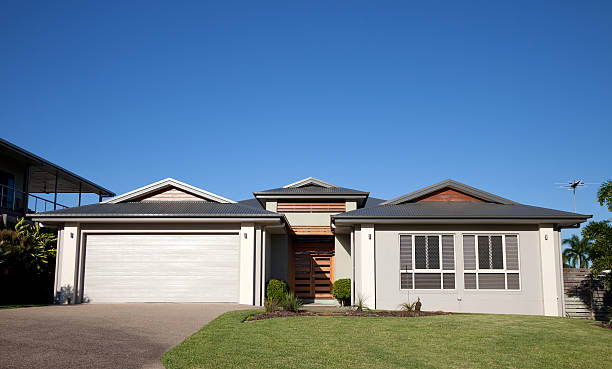 front of modern home with green grass and blue sky - bungalow stock photos and pictures