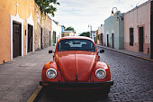 Merica, Yucatan, Mexico - 28 October 2018 - Front of red Oldtimer Volkswagen Beetle in the colonial historical streets at 'Casa Culcal Kin'