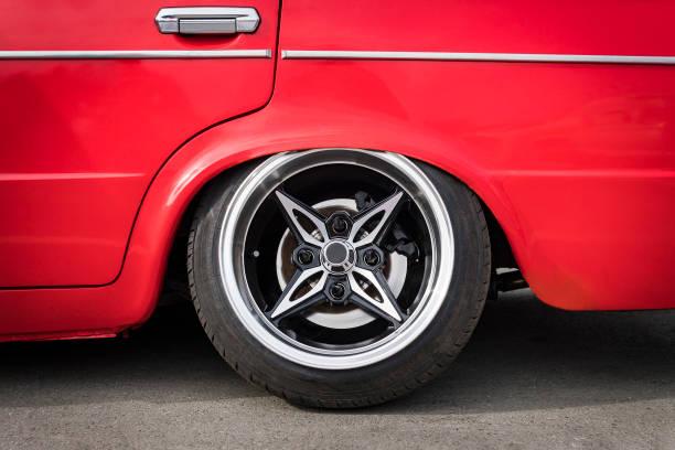die front des autos die tieferlegung zu boden anpassen. seitliche sicht auf neue luxus-auto-rad auf silber metall felge mit reifen schwarzen glanz. luxus-sport-auto-rad mit low-profile-reifen. auto-tuning - alufelgen stock-fotos und bilder