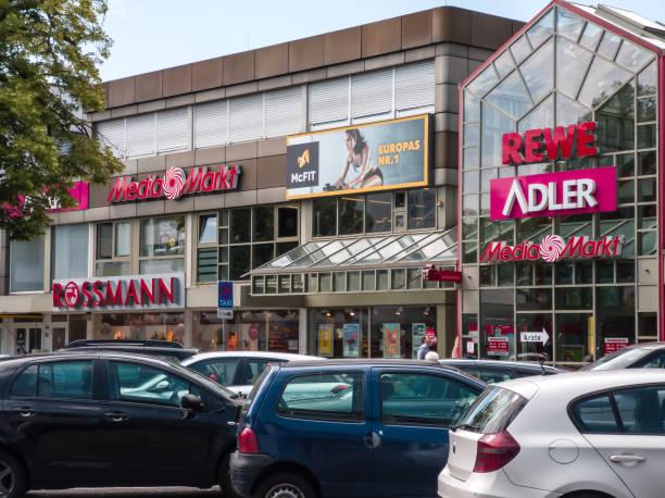 vor dem einkaufszentrum mit marken von adler, mcfit, media markt, rewe und rossmann - rewe germany stock-fotos und bilder