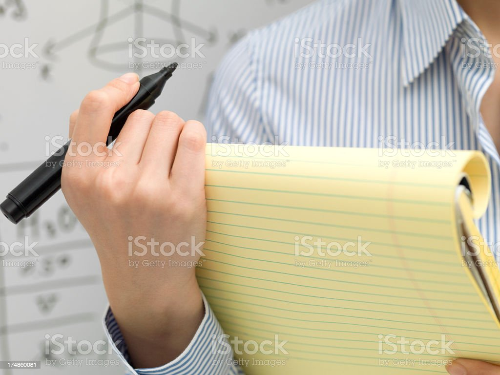 Front of the whiteboard, woman standing holding a note. royalty-free stock photo
