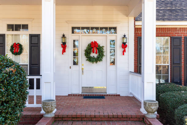 Front Porch and door decorated for the Christmas holiday season Residential home front door decorated for Christmas front door stock pictures, royalty-free photos & images