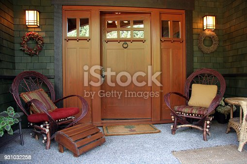 Front porch and entrance of home.  Lights on. Front door ajar. Bent Willow chairs and cushions. Wreaths on either side of door.
