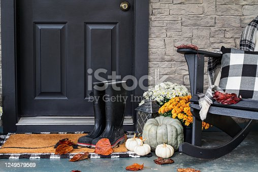 Traditional style front porch decorated for autumn with rain boots, heirloom gourds,  white pumpkins, mums and rocking chair with buffalo plaid pillow and throw blanket giving an inviting atmosphere.