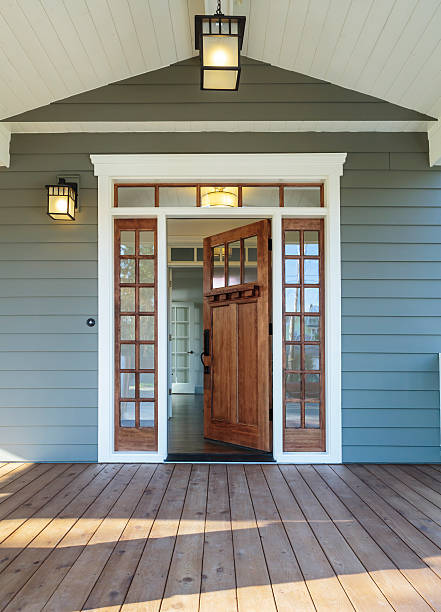 front porch of blue-gray house with open front door - building entrance stock photos and pictures