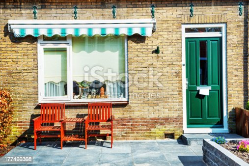 istock Front Porch of House with Green Door and Wooden Armchairs 177466368