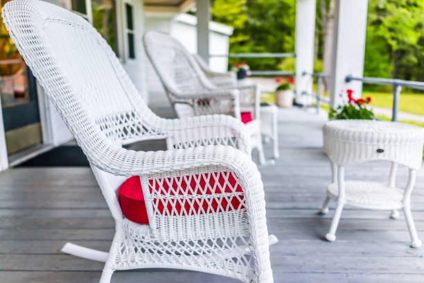 Front porch of house with white rocking chairs on wooden deck stock photo