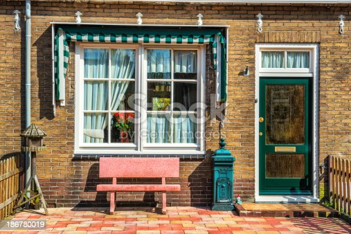 istock Front Porch of House with Wooden Door and Bench 186780019