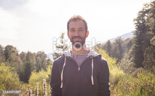 492529287istockphoto Front portrait of a young man with a beard in casual clothing in nature 1144031587