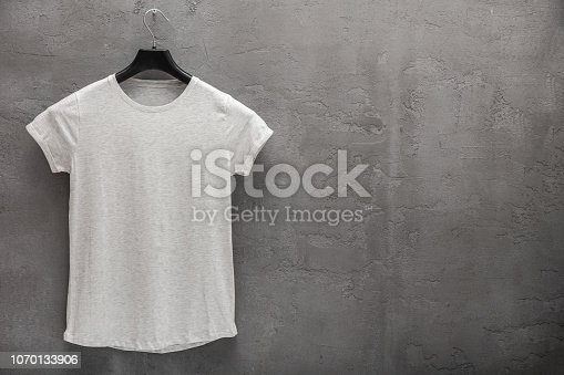 Front side of female grey melange cotton t-shirt on a hanger and a concrete wall in the background. T-shirt without print and copyspace for your text on right side