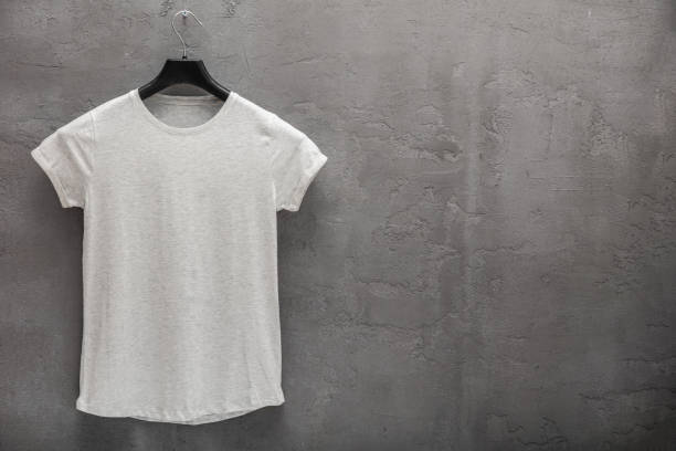 Front side of female grey melange cotton t-shirt on a hanger and a concrete wall in the background Front side of female grey melange cotton t-shirt on a hanger and a concrete wall in the background. T-shirt without print and copyspace for your text on right side coathanger stock pictures, royalty-free photos & images