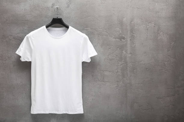 Front side of male white cotton t-shirt on a hanger and a concrete wall in the background Front side of male white cotton t-shirt on a hanger and a concrete wall in the background. T-shirt without print and copyspace for your text on right side coathanger stock pictures, royalty-free photos & images