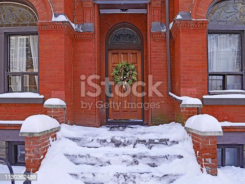 front steps of old brick building covered in snow, with seasonal wreath on wooden front door