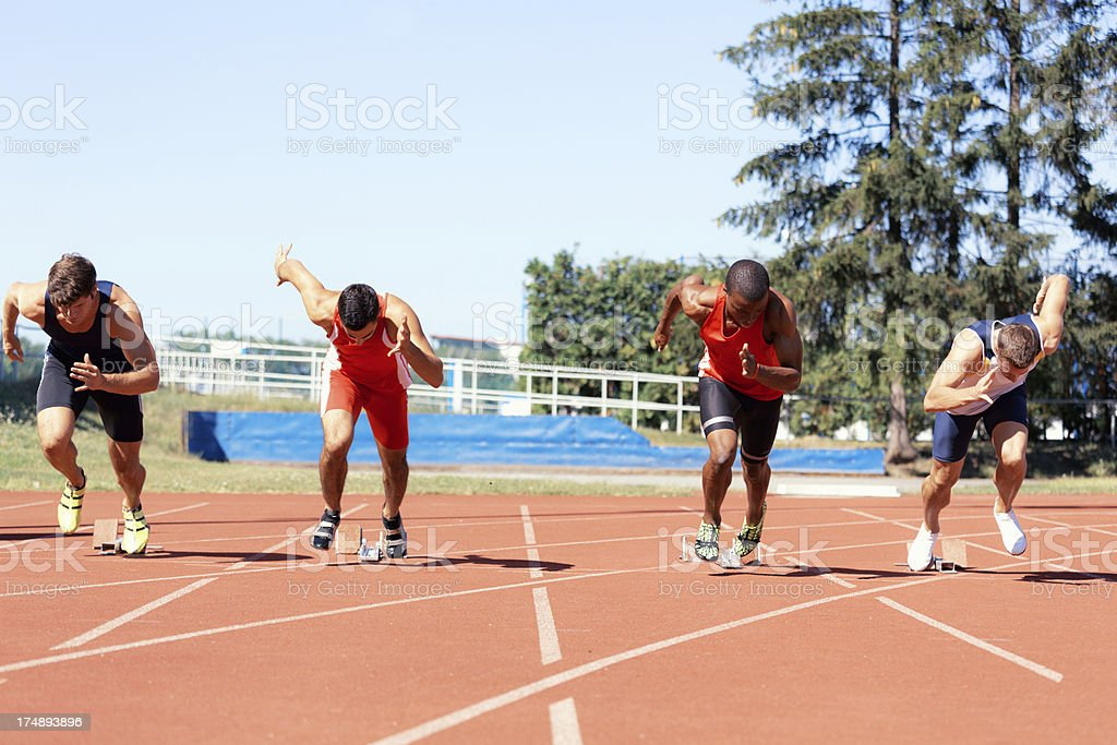 front view 100 meter start athletes stock photo