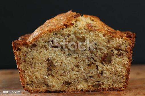 A close up horizontal photograph of the front of a  freshly baked banana bread loaf with one slice cut off revealing  the moist interior. Isolated on black.