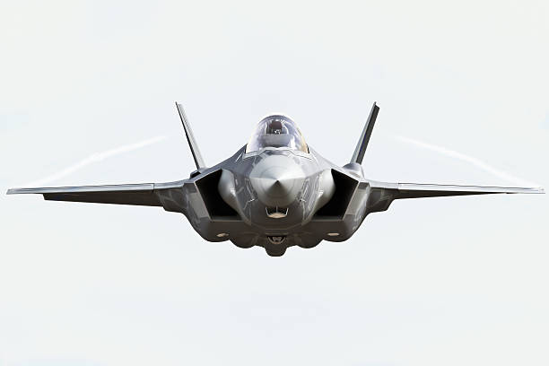F35 front view close up F35 front view close up flying to the camera with chem trails fighter plane stock pictures, royalty-free photos & images