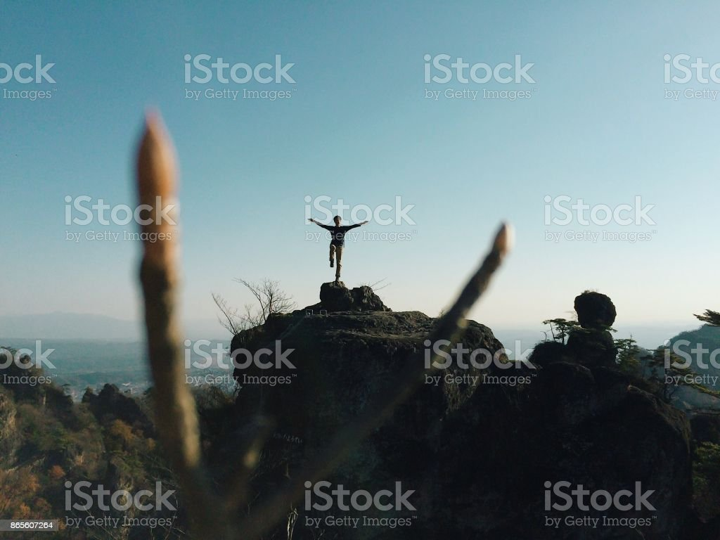 Front View Full Length Of Man Standing On One leg on Mountain Against...