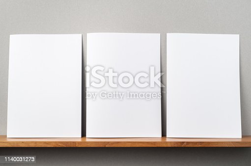 Design concept - front view of 3 A4 magazine stand on bookshelf and grey wall for mockup, not 3D render