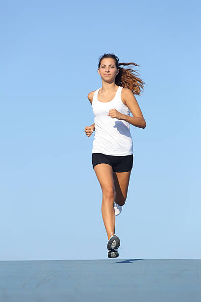 Front view of a beautiful sportswoman running towards camera Front view of a beautiful sportswoman running towards camera with the blue sky in the background approaching stock pictures, royalty-free photos & images