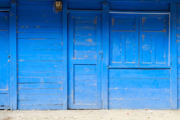 Vorderansicht eines blau lackierten Holzhauses mit geschlossener Tür, Fenster und Rollladen – Foto