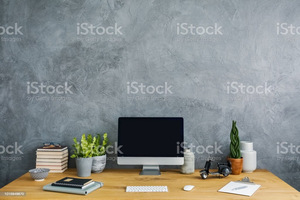 Front view of a desk with a computer, plants, notebooks and motorbike...