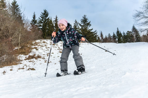 Front view of a girl skiing downhill surrounded by trees. stock photo