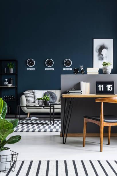 vorderansicht eines home-office interieurs mit schreibtisch, stuhl und wohnzimmer mit einem sofa und uhren an der wand - uhrenhalter stock-fotos und bilder