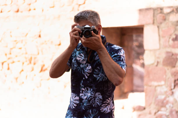 Front view of a man in Hawaiian shirt taking a photo with a vintage camera stock photo