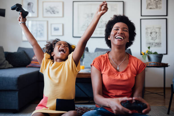 Front view of a mother and daughter playing video games together stock photo