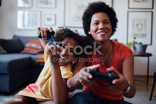 Young little African American girl with her African American mother spending some quality time together at home playing video games and having fun