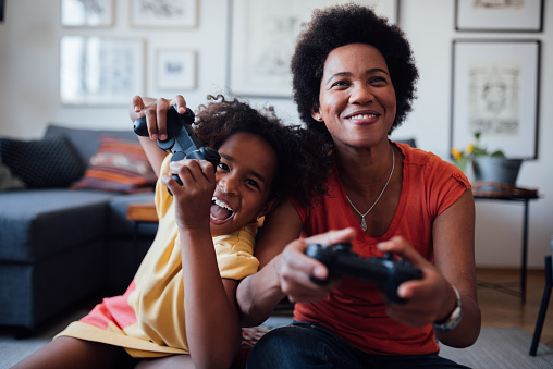 Front view of a mother and daughter playing video games together