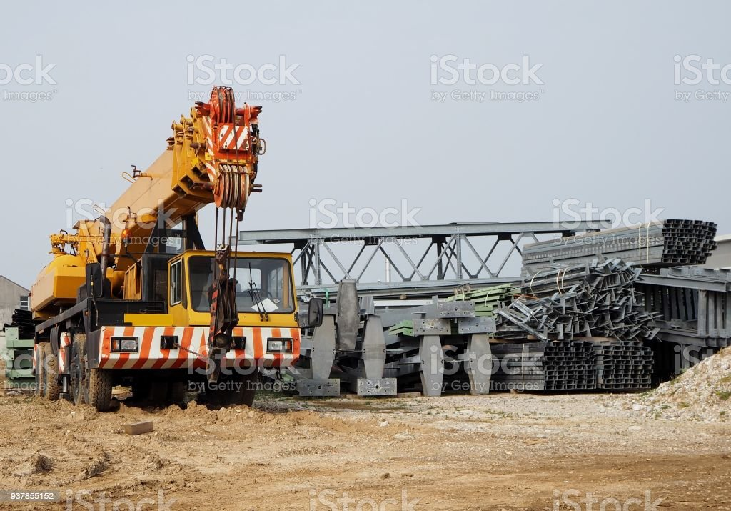 Front view of a telescopic crane truck  next to scaffolding and metal structures for the construction of a new building stock photo