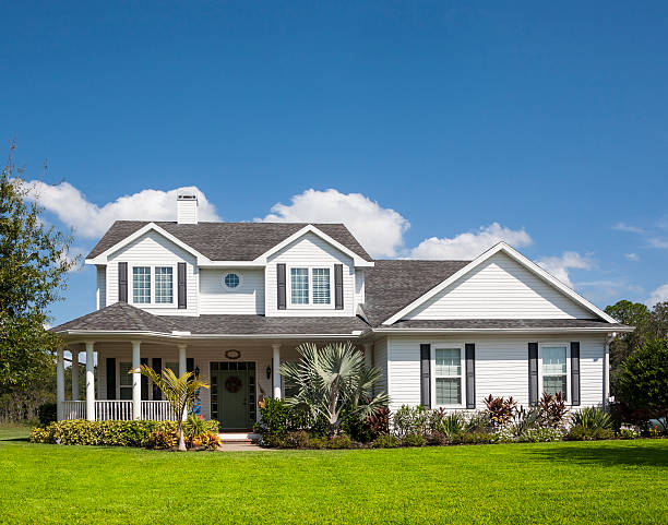 Front view of a Traditional American Home with wrapped porch Traditional American home with space for copy; blue sky, extensive front lawn. southern usa stock pictures, royalty-free photos & images