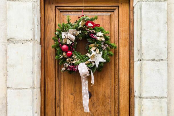 vorderansicht einer traditionellen weihnachts-krone aus immergrünen zweigen, rote weihnachtskugeln, holly blätter und beeren auf eine hölzerne eingangstür mit weißem kalkstein rahmen aufgehängt - türbänder stock-fotos und bilder