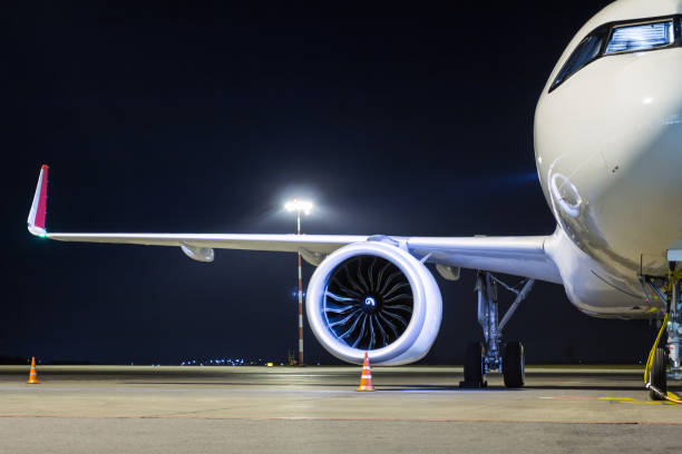 Frontansicht eines weißen Passagierflugzeugs, das an eine externe Stromversorgung an einem Nachtvorfeld des Flughafens angeschlossen ist – Foto
