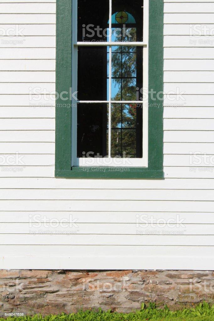 Vue de face d'une fenêtre dans un bâtiment d'église clin peint blanc coupé en vert - Photo