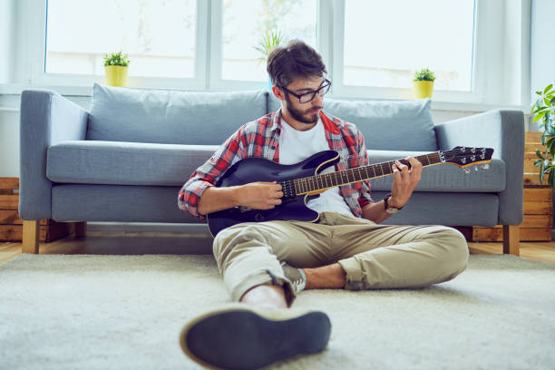 Front view of a young handsome man playing the guitar while sitting on floor in his living room stock photo