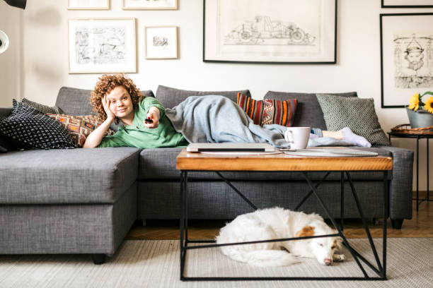Front view of a young redhead woman watching TV at home stock photo