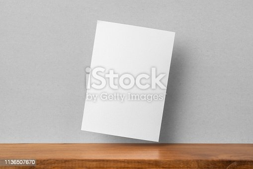 Design concept - front view of A4 paper on bookshelf and grey wall for mockup, not 3D render