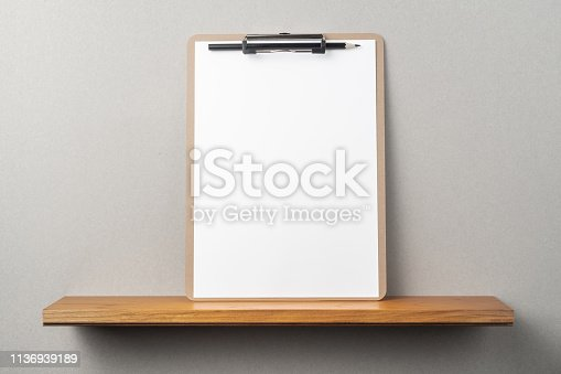 istock front view of A4 paper with clipboard on bookshelf 1136939189