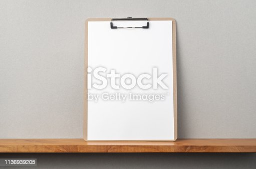 istock front view of A4 paper with clipboard on bookshelf 1136939205