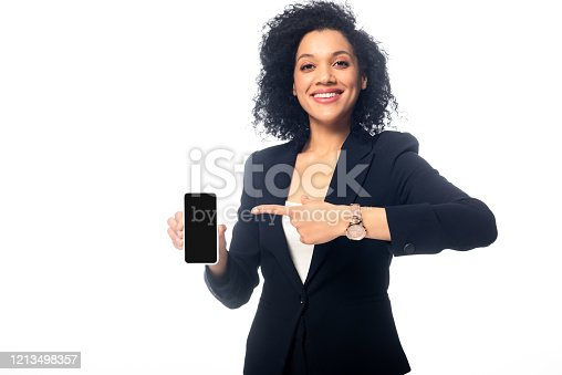 1159261513 istock photo Front view of african american woman pointing at smartphone, smiling and looking at camera isolated on white 1213498357