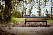 A lonely man sat on a park bench in Autumn by himself