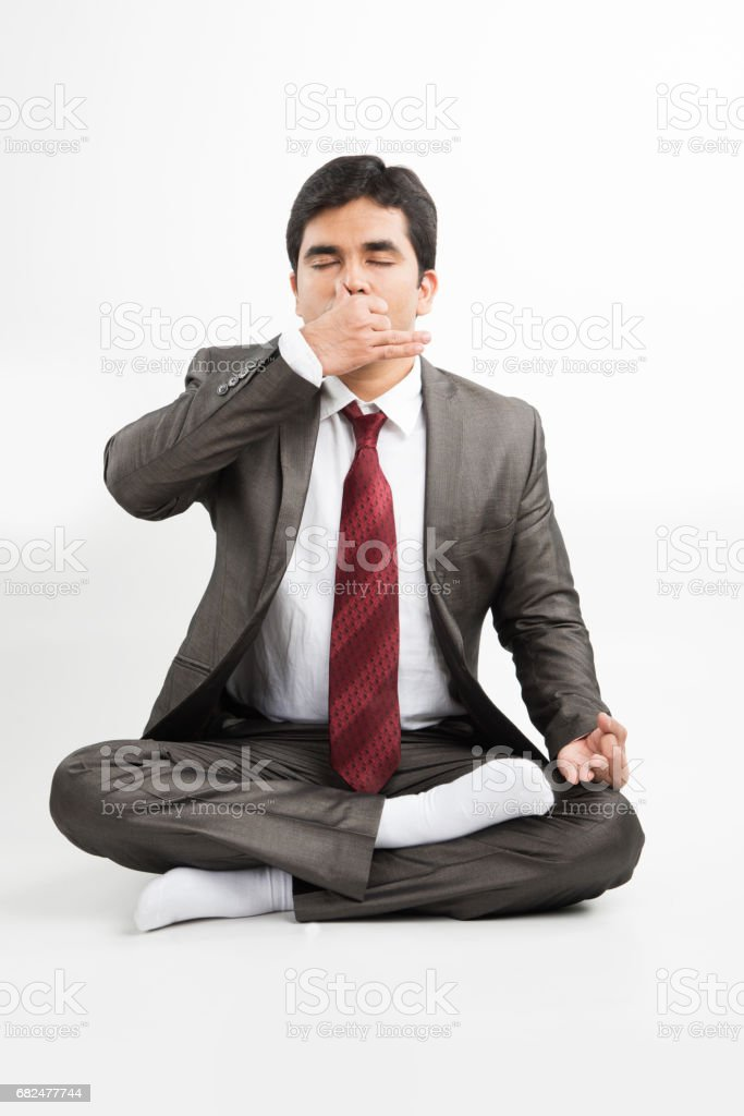 front view of an indian young businessman meditating or practicing yoga or pranayama or breathing exercise in corporate attire in the office or isolated over white background foto stock royalty-free