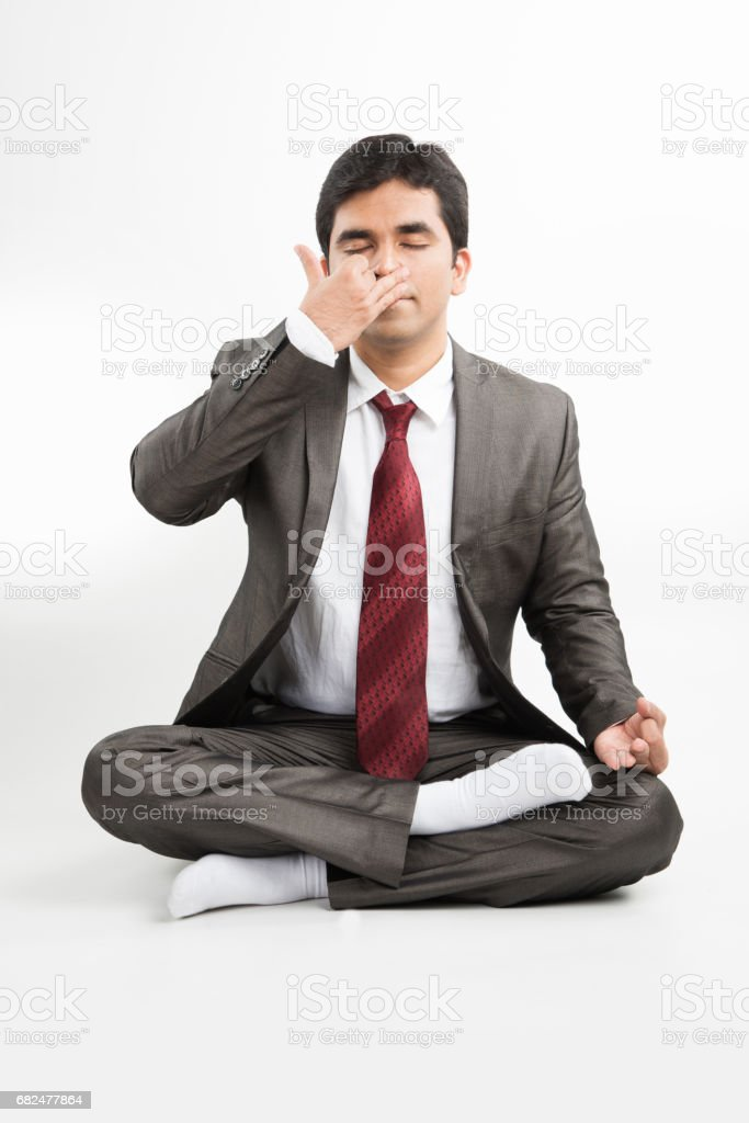 front view of an indian young businessman meditating or practicing yoga or pranayama or breathing exercise in corporate attire in the office or isolated over white background royalty free stockfoto