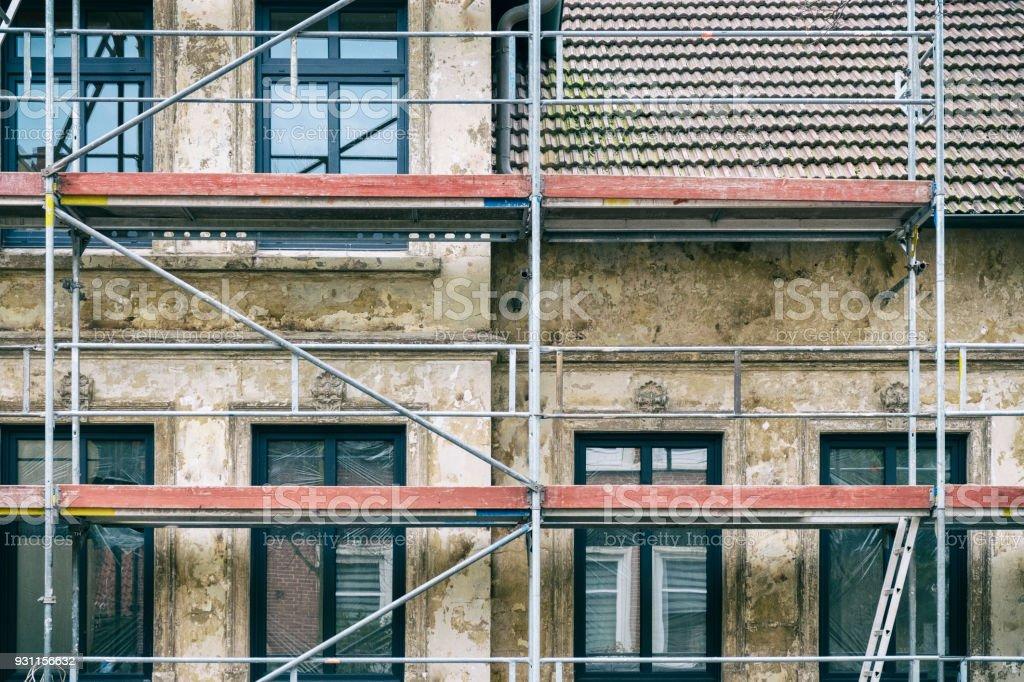 Vorderansicht eines alten Gebäudes während der Restaurierung und Sanierung mit neuen Fenstern – Foto