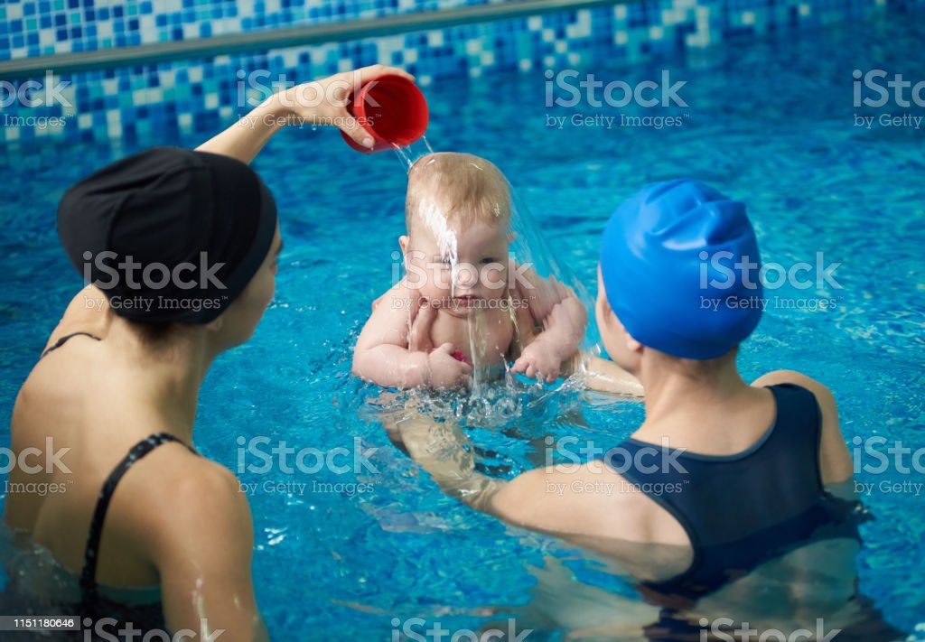 Front view of baby boy during swimming lesson. Back view of mother...