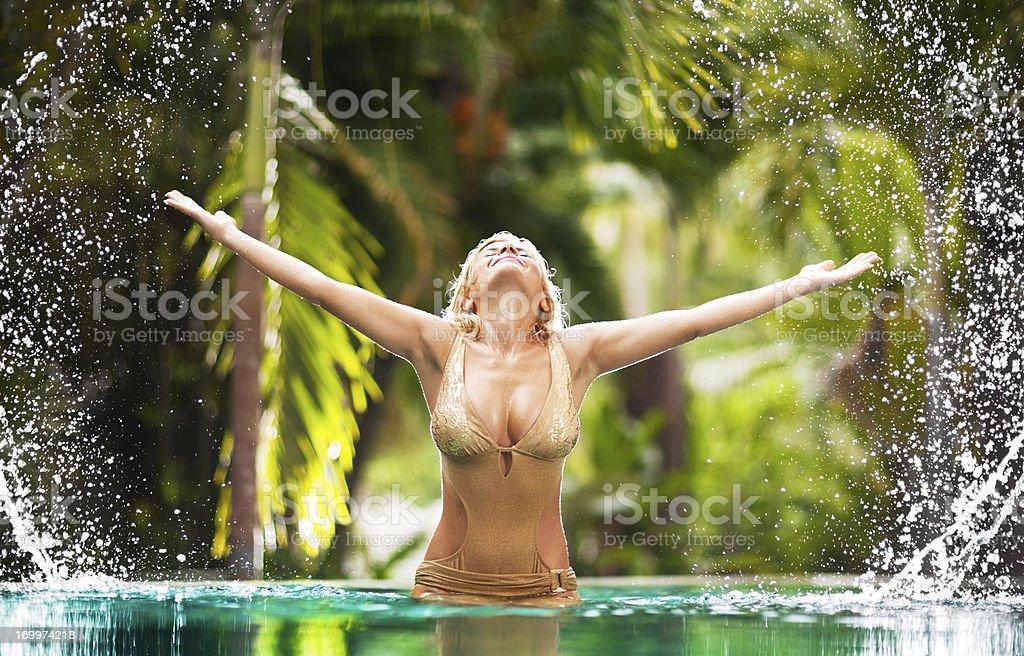 Front view of beautiful blonde splashing water in tropical resor royalty-free stock photo